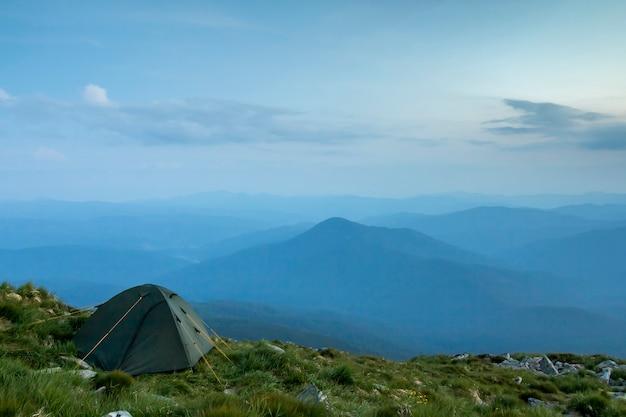 새벽에 산에서 여름 캠핑입니다. 일출 또는 일몰 전에 분홍색 하늘 아래 먼 안개 낀 푸른 산 범위에 둥근 잔디 언덕에 관광 텐트. 관광, 하이킹 및 자연 컨셉의 아름다움.
