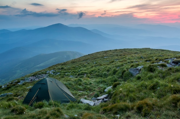 Summer camping in mountains at dawn. tourist tent on round grassy hill on distant misty blue mountains range under pink sky before sunrise or sunset. tourism, hiking and beauty of nature concept.