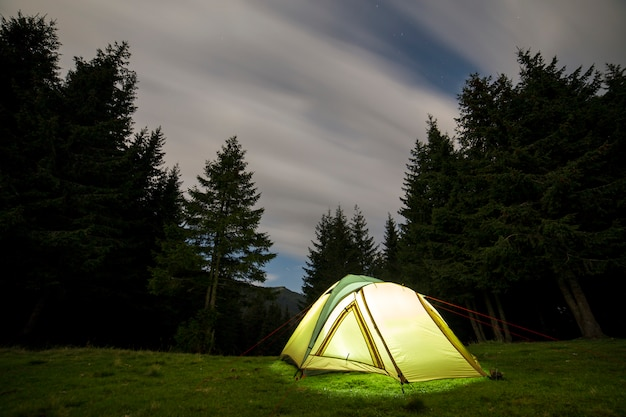 Summer camping at night. illuminated tourist tent on green clearing on distant mountain .