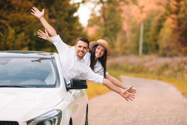 Летняя автомобильная поездка и двое молодых людей. счастливая семья смотрит из машины и веселится
