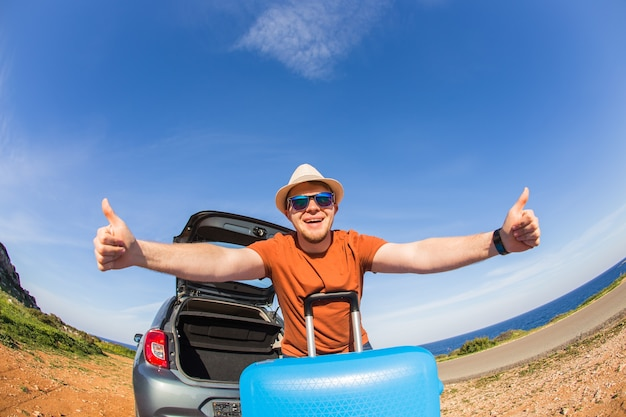 Summer, car, trip and vacation concept. happy traveler sitting in car open trunk and showing thumbs up.