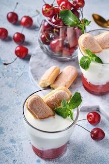 Летнее вишневое слоеное тесто с печеньем савоярди и сливочным сыром в стекле на светло-сером фоне. традиционный торт тирамису со свежими ягодами. выборочный фокус.
