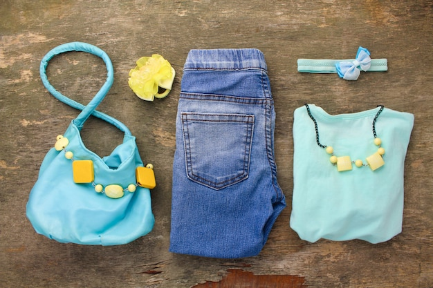 Summer children's clothing: t-shirt, jeans, handbag, beads.