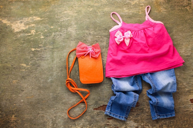 Summer children's clothing: t-shirt, jeans, handbag. top view.