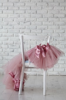 Summer children's dresses hang on hangers on the back children's chair. place for text