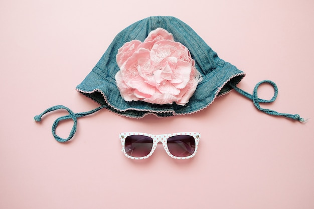 Summer childrens denim hat and sunglasses on pink background