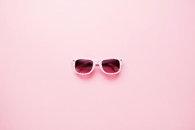 Summer childrens sunglasses on pink background