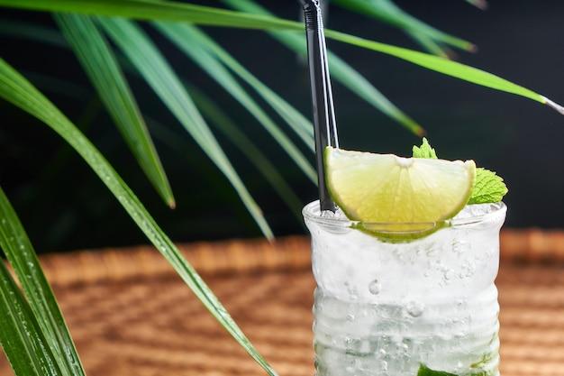 Летние охлажденные напитки со свежевыжатым соком, мятой, льдом на плетеном столе с листьями