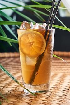 Летние охлажденные напитки со свежим апельсиновым соком и колой на плетеном столе с листьями