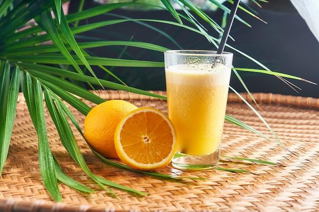 Летние охлажденные напитки со свежим апельсиновым соком с апельсинами на плетеном столе с листьями
