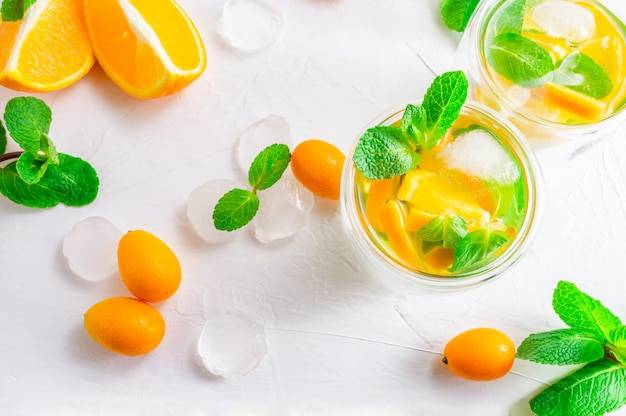Summer citrus drink with orange, kumquat, mint and ice cubes on white background. flat-lay, top view.