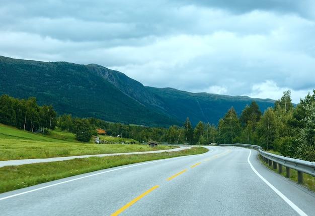 道路(ノルウェー)と夏の曇り山の風景。