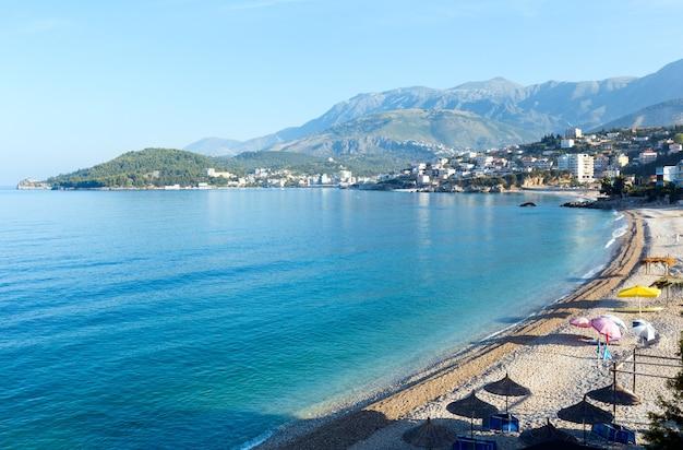 Летнее побережье, утро, вид на город химара с галечным пляжем (албания)