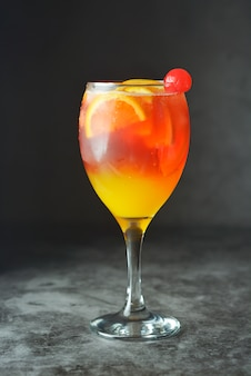 Summer cocktail. orange juice with mint, syrop, fruit slices and cherry with ice.