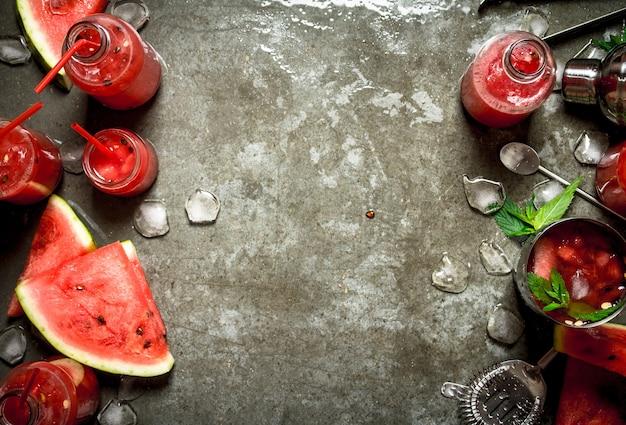 夏のカクテル。石のテーブルの上のシェーカーでミントと氷とスイカのスライス。