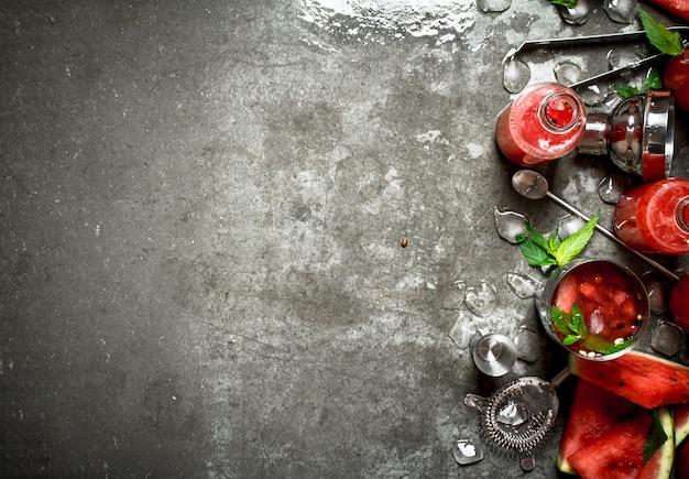 夏のカクテル。シェーカーにミントと氷を入れたスイカのスライス。石のテーブルの上。
