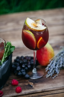 Summer cocktail with fruits on wooden table
