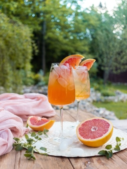 Summer cocktail with grapefruit flowers and ice