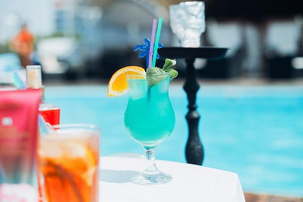 スイミングプールの背景に水ギセルと夏のカクテル