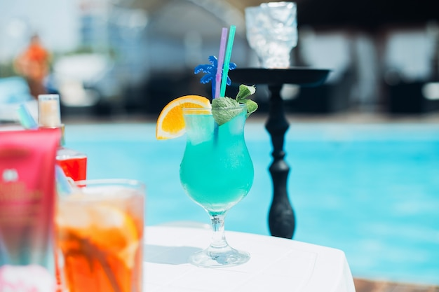 Summer cocktail with hookah on swimming pool background