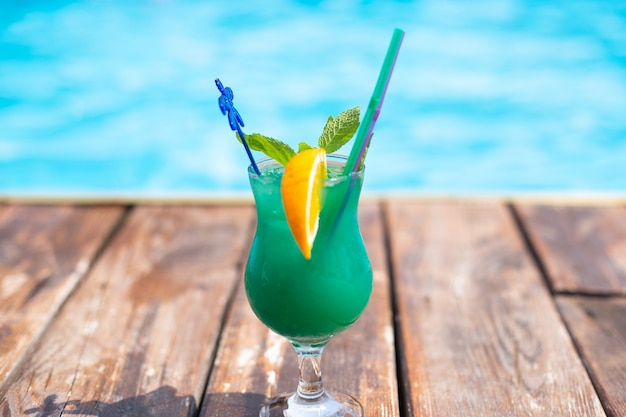 Summer cocktail with lime orange and mint on beach background
