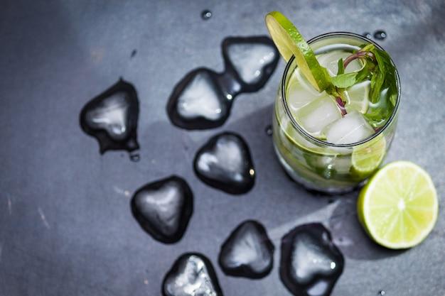 Летний коктейль мохито со льдом, мята, лайм на сером фоне. копировать пространство