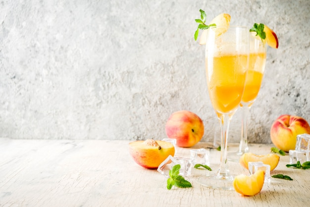 Summer cold alcohol beverage, iced peach bellini cocktail with mint leaves, light concrete background