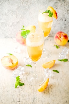 Summer cold alcohol beverage, iced peach bellini cocktail with mint leaves, light concrete surface