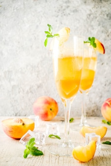 Summer cold alcohol beverage, iced peach bellini cocktail with mint leaves, light concrete wall