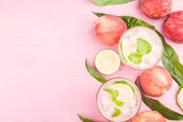 Summer cold alcohol beverage, iced peach bellini cocktail with mint leaves