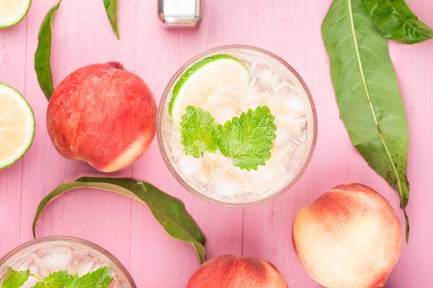 Summer cold alcohol beverage, iced peach bellini cocktail with mint leaves,