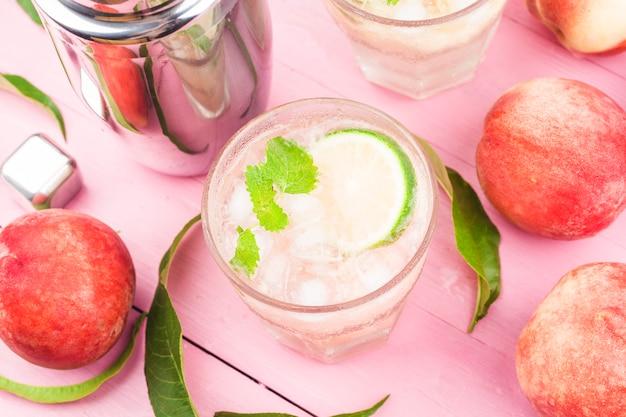 Летний холодный алкогольный напиток, ледяной персиковый коктейль беллини с листьями мяты,