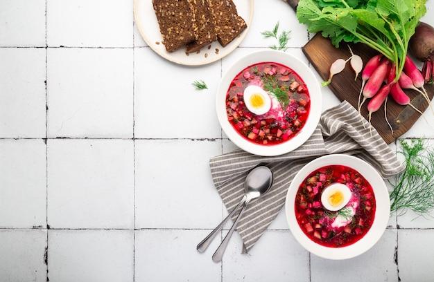 Летний холодный свекольный суп со сметаной и яйцом на фоне белой плитки русская кухня