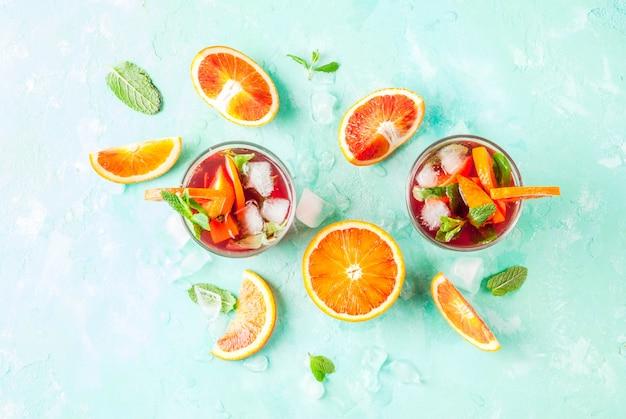 夏の冷たい飲み物、ブラッドオレンジミントカクテルミモザ、モヒートまたはサングリア、ライトブルー、copyspaceトップビュー