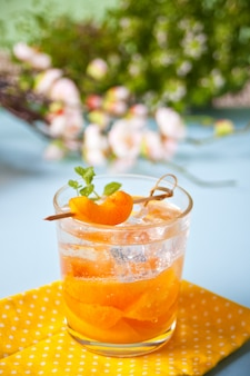 Summer cold drink homemade apricot lemonade ice tea with ice cubes and mint.