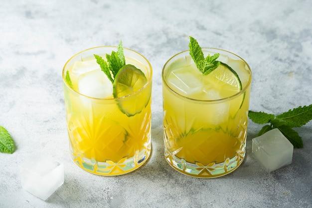 Летний холодный напиток с кубиками льда, соком и фруктами лайма, летний прохладительный напиток. цитрусовый вкусный сок.