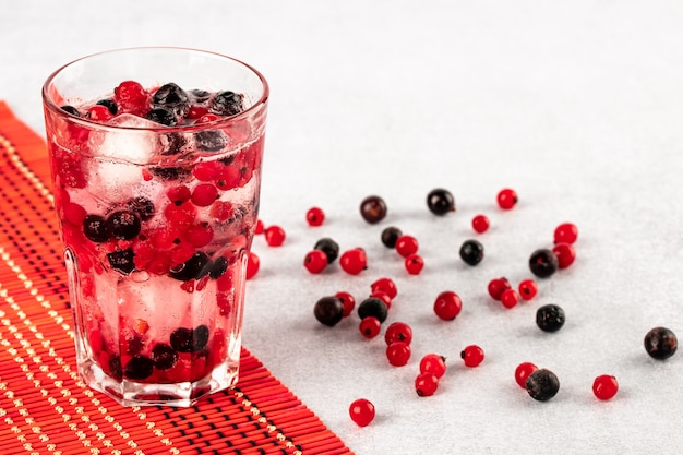 Летний холодный напиток с водой, льдом и разноцветными ягодами на красном кухонном сгустке и белом столе