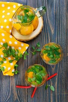 夏の冷たい飲み物。アプリコットと木製のテーブルにグラスにミントのおいしいさわやかなドリンク。果物のコンポート。フラットレイ。上面図。