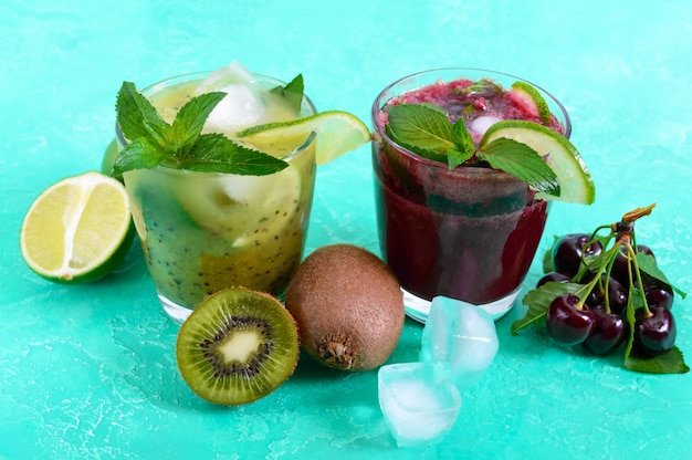 Летние прохладительные напитки со свежими фруктами, ягодами и мятой. вишневый смузи, коктейль из киви в бокалах.