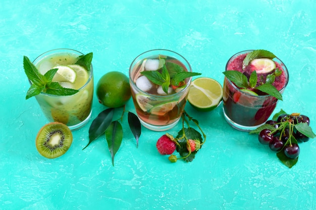 Летние прохладительные напитки со свежими фруктами, ягодами и мятой. клубничный мохито, вишневый смузи, коктейль из киви в бокалах.