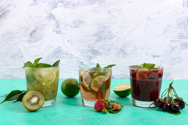 Summer cold drinks with fresh fruits, berries and mint. strawberry mojito, cherry smoothies, cocktail of kiwi in glasses .