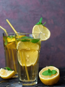 Summer cold homemade mojito tea with mint and lemon and ice