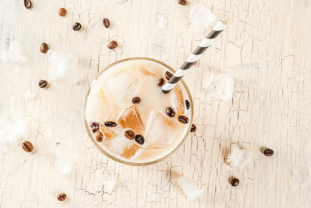 Summer cold iced coffee frappe with milk and ice cubes light concrete background above