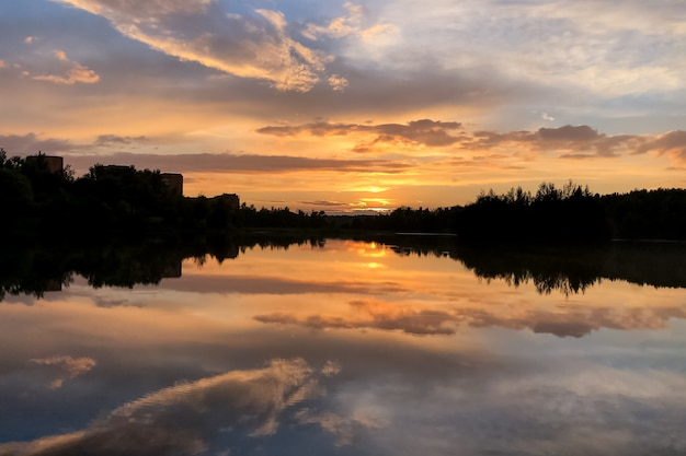 Летний красочный закат на озере с облаками, отраженными в воде
