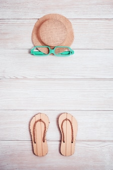 Summer composition, beach slippers, straw yellow hat, sunglasses on white wood. pastel colored. vacation by sea.