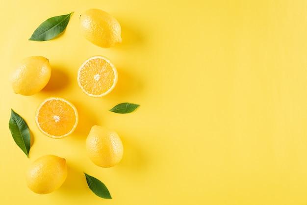 노란 종이에 오렌지, 레몬, 녹색 잎으로 만든 여름 구성