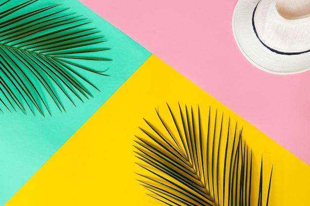 여름 구성 야자수 잎과 여름 모자는 노란색 분홍색과 청록색 질감 휴가 개념 탑 뷰 트렌디한 플랫 레이