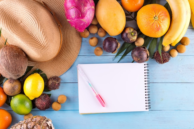 Summer composition. tropical palm leaves, hat, many fruits on blue wooden background.