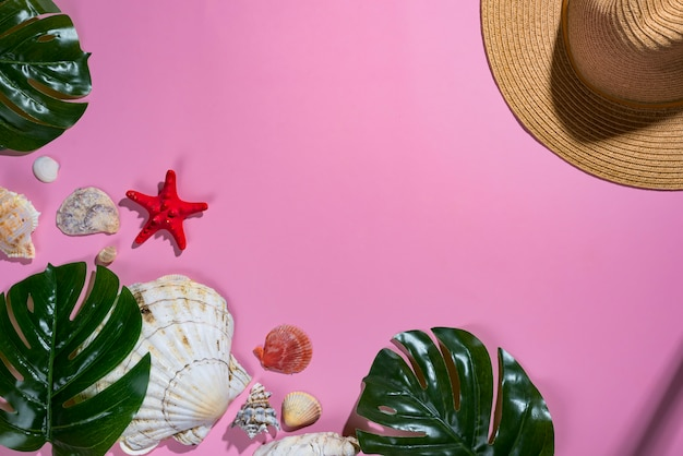 Summer composition. tropical palm leaves, hat, seashells on pastel violet background.