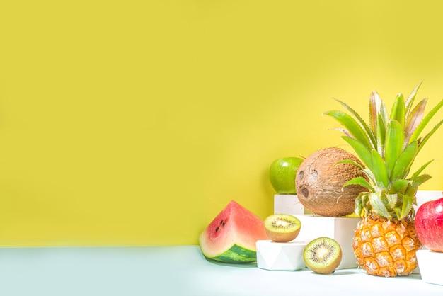 연단이 있는 현대적인 밝은 노란색 배경에 있는 다양한 열대 과일, 여름 구성, 복사 공간. 휴일 및 휴가, 건강 식품 개념 복사 공간